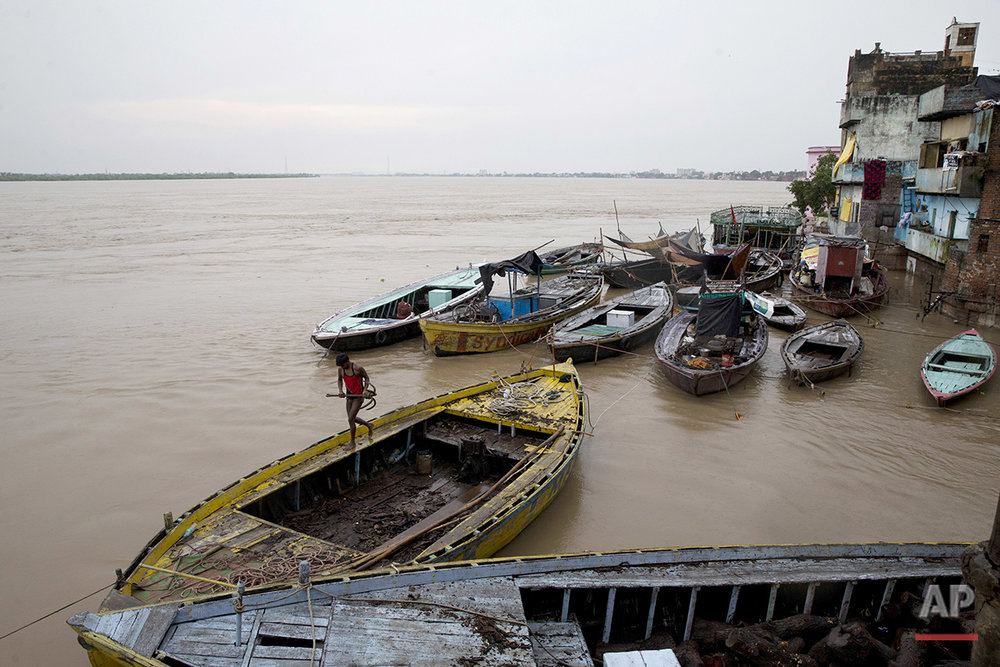 In this Friday, Aug. 26, 2016 photo, boats are docked at the Manikarnika Ghat, submerged by the flood waters in Varanasi, India. As the mighty Ganges River overflowed its banks this past week following heavy monsoon rains, large parts of the Hindu holy town of Varanasi were submerged by floodwaters, keeping away thousands of Hindu devotees. Devout Hindus believe that if they are cremated on Varanasi's ghats, or steps leading to the river, they earn immediate salvation and are freed from the cycle of birth and death. (AP Photo/Tsering Topgyal) See these photos on  APImages.com