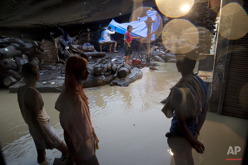 In this Friday, Aug. 26, 2016 photo, funeral service employees work on a flooded area near the Manikarnika Ghat in Varanasi, India. As the mighty Ganges River overflowed its banks this past week following heavy monsoon rains, large parts of the Hindu holy town of Varanasi were submerged by floodwaters, keeping away thousands of Hindu devotees. Varanasi is a pilgrim town that Hindus visit to take a dip in the holy Ganges. (AP Photo/Tsering Topgyal) See these photos on  APImages.com