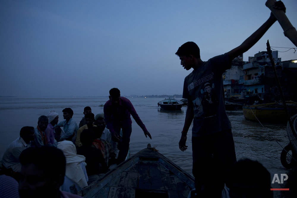 In this Thursday, Aug. 25, 2016 photo, Hindu mourners sit on a boat at the Manikarnika Ghat, on the banks of the Ganges river in Varanasi, India. As the mighty Ganges River overflowed its banks this past week following heavy monsoon rains, large parts of the Hindu holy town of Varanasi were submerged by floodwaters, keeping away thousands of Hindu devotees. Devout Hindus believe that if they are cremated on Varanasi's ghats, or steps leading to the river, they earn immediate salvation and are freed from the cycle of birth and death. (AP Photo/Tsering Topgyal) See these photos on  APImages.com