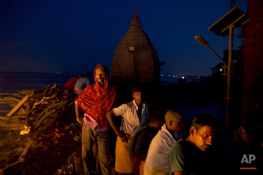 In this Thursday, Aug. 25, 2016 photo, Hindu mourners attend the cremation at the flooded Manikarnika Ghat in Varanasi, India. As the mighty Ganges River overflowed its banks this past week following heavy monsoon rains, large parts of the Hindu holy town of Varanasi were submerged by floodwaters, keeping away thousands of Hindu devotees. Varanasi is a pilgrim town that Hindus visit to take a dip in the holy Ganges. (AP Photo/Tsering Topgyal) See these photos on  APImages.com