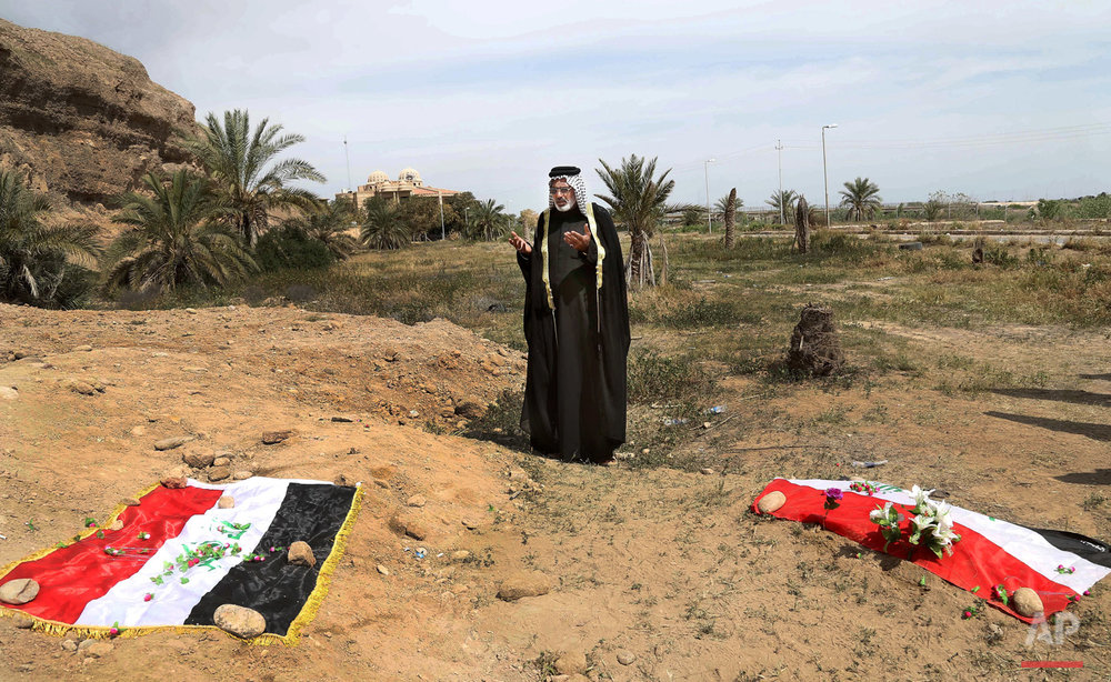 In this April 3, 2015, photo, an Iraqi man prays for his slain relative at the site of a mass grave believed to contain the bodies of Iraqi soldiers killed by Islamic State group militants when they overran Camp Speicher military base in Tikrit, Iraq, in June 2014. An analysis by The Associated Press has found 72 mass graves left behind by Islamic State extremists in Iraq and Syria, and many more are expected to be discovered as the group loses territory. (AP Photo/Khalid Mohammed)