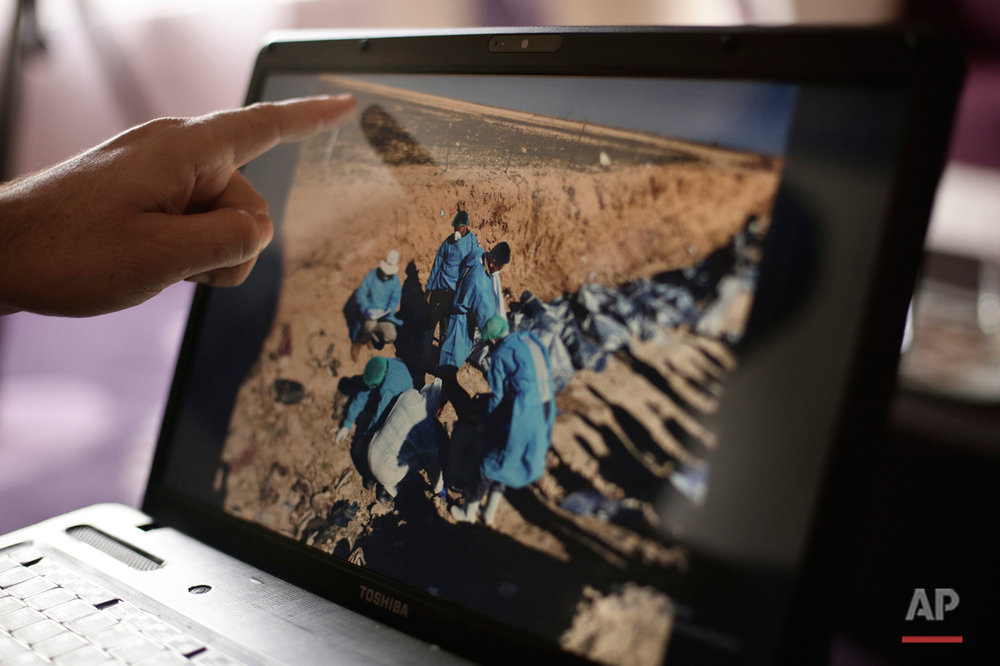 In this May 17, 2016 photo, Sirwan Jalal, Director of Mass Graves for the Kurdish Regional Government, points to an image of the site of a mass grave during an interview with the Associated Press in Irbil, northern Iraq.  An analysis by The AP has found 72 mass graves left behind by Islamic State extremists in Iraq and Syria, and many more are expected to be discovered as the group loses territory. (AP Photo/Maya Alleruzzo)