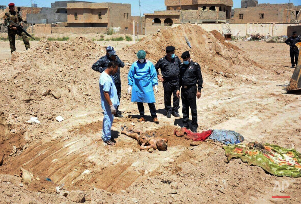 In this April 19, 2016 photo, an Iraqi security forces forensic team works at the site of a mass grave believed to contain the bodies of Iraqi civilians, security forces and members of their families, including women and children, killed by Islamic State group militants at the stadium area in Ramadi, Iraq. An analysis by The Associated Press has found 72 mass graves left behind by Islamic State extremists in Iraq and Syria, and many more are expected to be discovered as the group loses territory. Only a handful have been exhumed. (AP Photo)