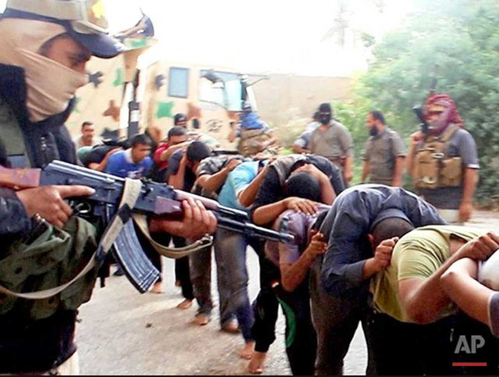 This image posted online by Islamic State militants on June 14, 2014 shows Iraqi cadets captured by IS moments before they were killed in Tikrit, Iraq. Their bodies are believed to be in one of the many mass graves left behind by Islamic State extremists. An analysis by The Associated Press has found 72 such graves in Iraq and Syria, and many more are expected to be discovered as the group loses territory.  (Militant photo via AP)