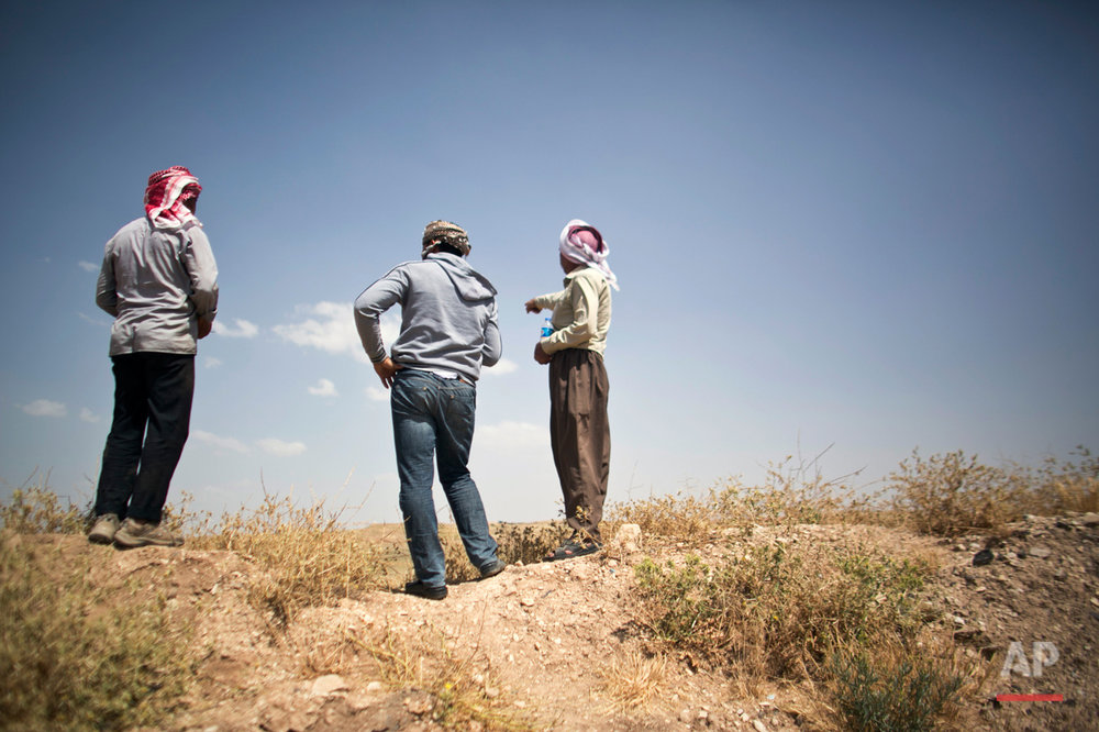 In this May 19, 2016 photo, Arkan Qassim, center, looks at the site where he witnessed the killing dozens of Yazidi men in August 2014 in Hardan, northern Iraq. Rasho Qassim, right, lost two sons in the massacre. Both survivors say they simply want the graves exhumed. (AP Photo/Maya Alleruzzo)