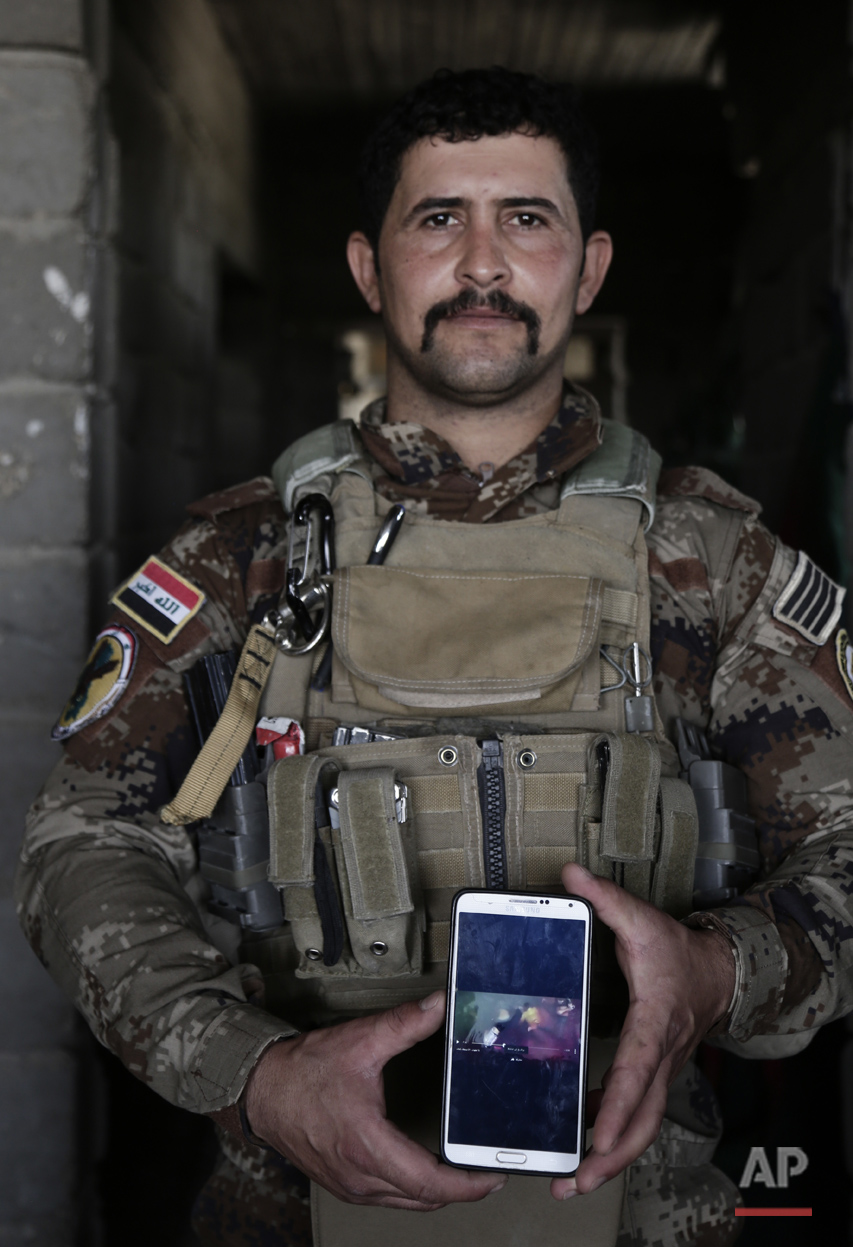 In this June 8, 2016 photo, Sgt. Ahmed Abdelaziz of Iraq's elite counterterrorism forces shows an Islamic State video of his brother's death at the hands of the IS at a battle position on the southern edge of Fallujah, Iraq. Saad Abdelaziz was killed in June 2014 at Camp Speicher when the militants overran his base. More than 1,000 of Saad's comrades killed in the massacre ended up in a mass grave nearby. An analysis by The Associated Press has found 72 mass graves left behind by Islamic State extremists in Iraq and Syria, and many more are expected to be discovered as the group loses territory. (AP Photo/Maya Alleruzzo)
