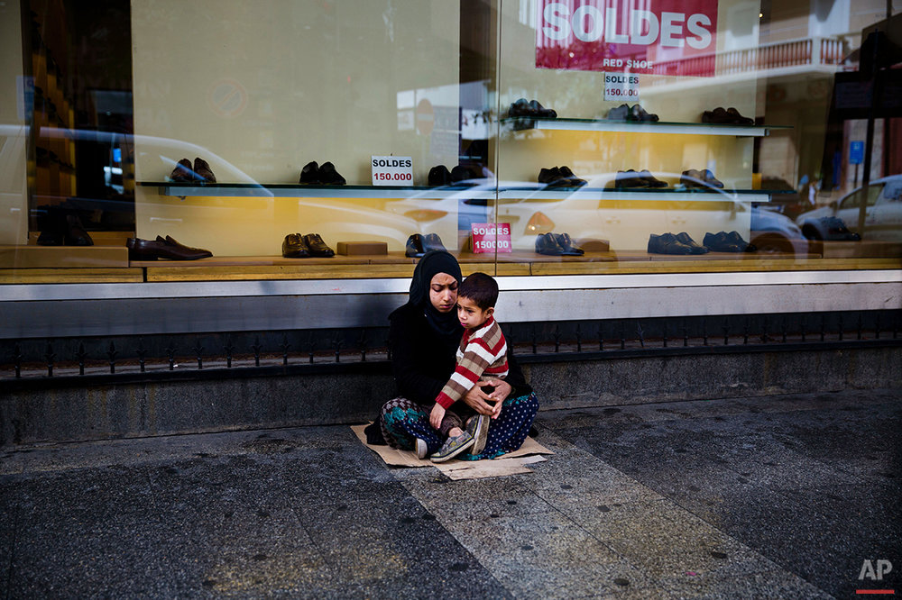 In this Tuesday, March 15, 2016 photo, a Syrian refugee woman holds her child as she begs for money on a sidewalk, in Beirut. Lebanon is home to more than 1 million registered Syrian refugees, or nearly a quarter of the country's 4.5 million people, the highest refugee population in the world per capita. It is one of the most visible signs of the refugee crisis that has put an immense strain on neighboring countries and destabilized Europe. On Lebanon shopping streets beggars are seen stretching their hands out for money. (AP Photo/Hassan Ammar)
