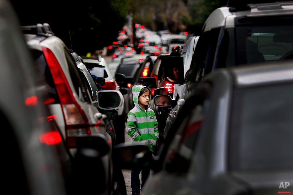 In this Wednesday, Feb. 10, 2016 photo, a Syrian refugee girl begs for money in traffic, in Beirut. A study published last year by the International Labor Organization, UNICEF and the Save the Children charity organization found there are more than 1,500 children living or working on Lebanon's streets, nearly three-quarters of them Syrian and most making a living by begging or roadside vending. (AP Photo/Hassan Ammar)