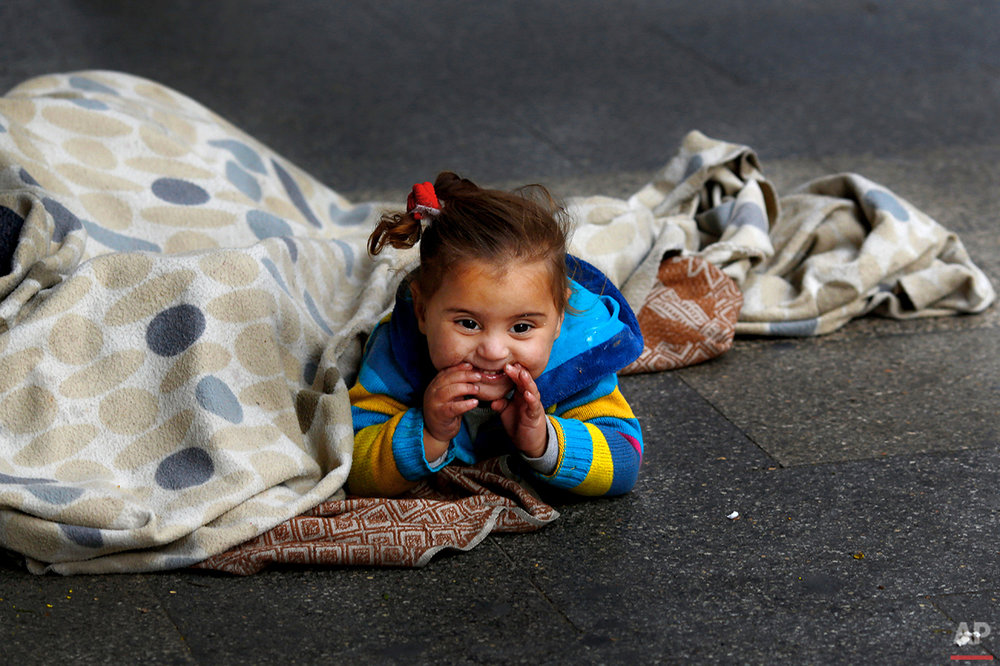 In this Wednesday, Feb. 10, 2016 photo, a Syrian refugee girl sits on the sidewalk with her mother as they beg for money, in Beirut. A study published last year by the International Labor Organization, UNICEF and the Save the Children charity organization found there are more than 1,500 children living or working on Lebanon's streets, nearly three-quarters of them Syrian and most making a living by begging. (AP Photo/Hassan Ammar)