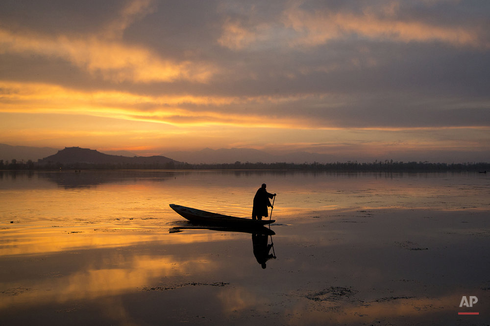 A Kashmiri fisherman rows his Shikara, or traditional boat, during sunset at the Dal Lake in Srinagar, Indian controlled Kashmir, Tuesday, March 29, 2016.  Nestled in the Himalayan mountains and known for its beautiful lakes and saucer-shaped valleys, the Indian portion of Kashmir, is also one of the most militarized places on earth. (AP Photo/Dar Yasin)
