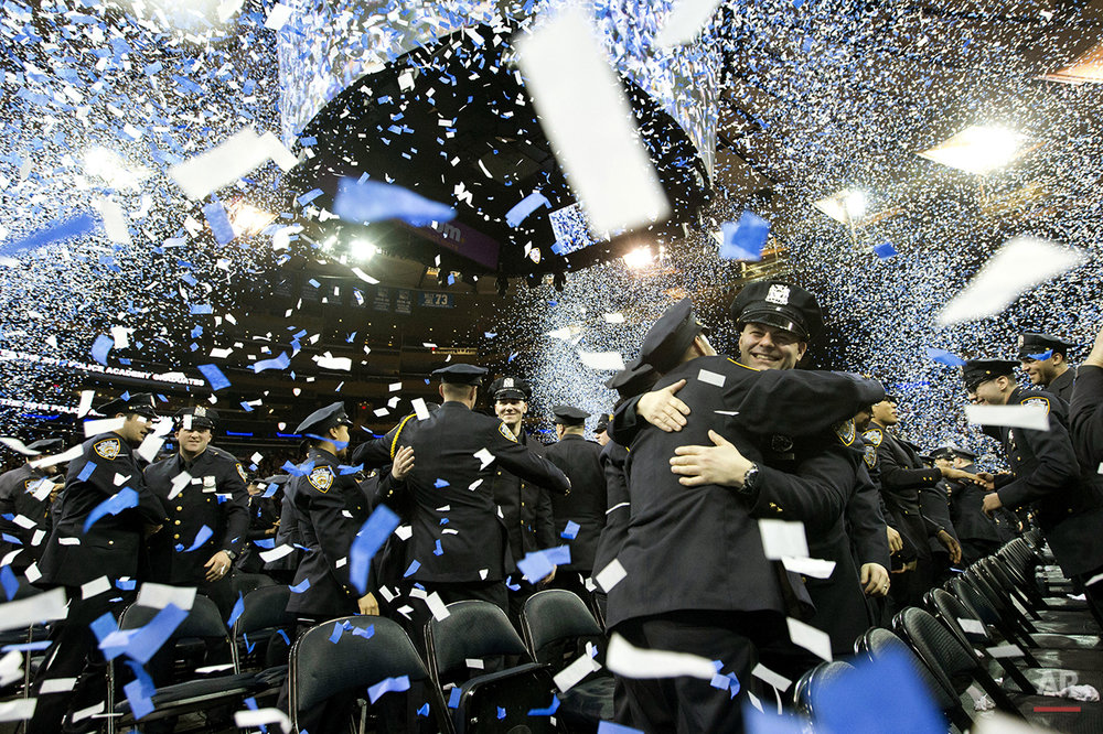 New police officers embrace at the end of the New York City Police Department Police Academy graduation ceremony, Friday, April 1, 2016, at Madison Square Garden in New York. (AP Photo/Mary Altaffer)