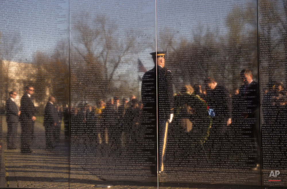 Defense Secretary Ash Carter, right and Veterans Affairs Secretary Robert McDonald are reflected in the Vietnam Memorial Wall as they bow there heads in silence to during a wreath laying ceremony to mark the 50th anniversary of the Vietnam War in Washington, Tuesday, March 29, 2016.  (AP Photo/Molly Riley)