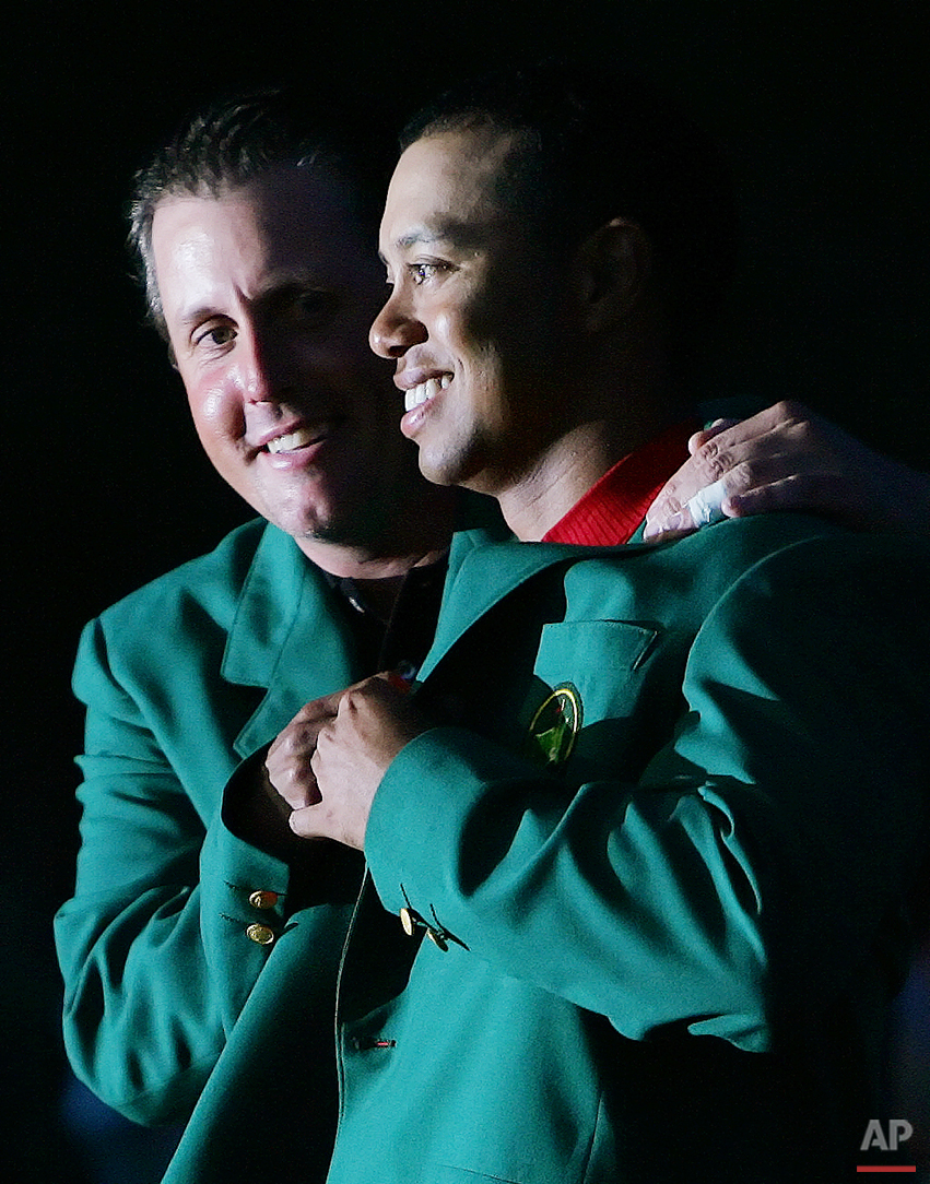 Phil Mickelson, left, last years Masters champion, puts the Green Jacket on Tiger Woods, right, after Woods won the 2005 Masters in a playoff at the Augusta National Golf Club in Augusta, Ga., in this April 10, 2005 photo. (AP Photo/David J. Phillip)