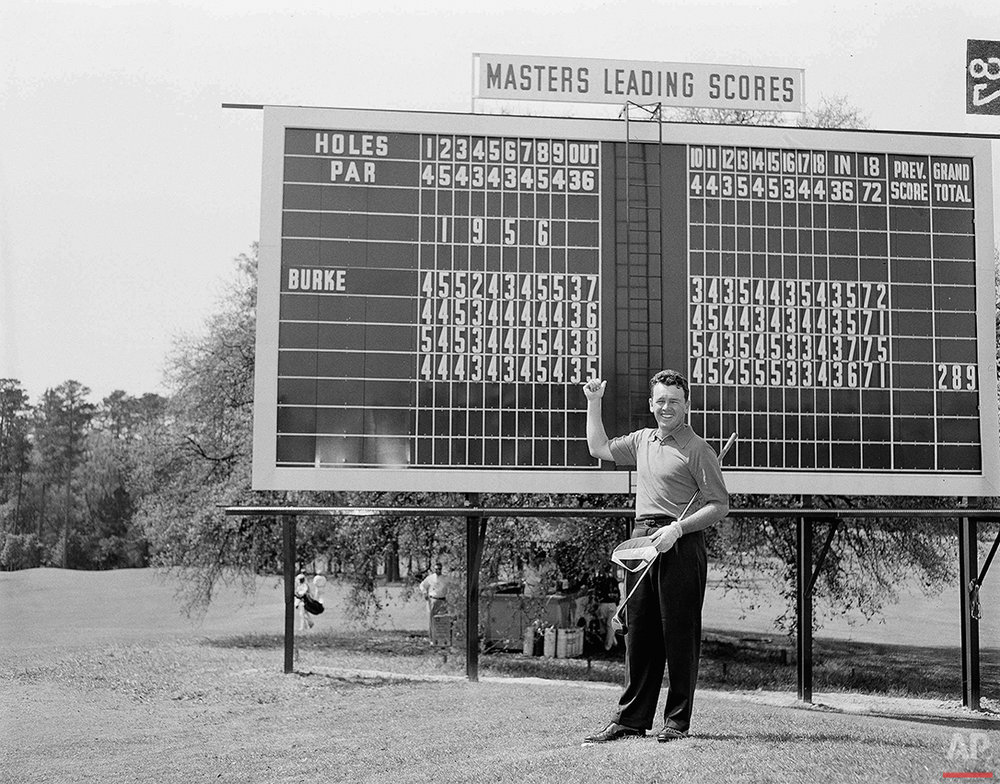 Defending Masters champ Jack Burke Jr. points a thumb to his 1956 winning round scores which are posted along the No. 1 fairway of the Augusta National Golf Club, April 3, 1957. Burke surged from behind last year and overtook Ken Venturi on the last day with a total 289.  (AP Photo/Horace Cort)