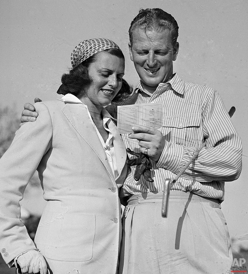 In this April 6, 1941 photo, Craig Wood and his wife smile as they admire his score card after winning the Master golf tournament in Augusta, Ga. Wood went wire-to-wire to win his first major and a check for $1,500. (AP Photo/B.I. Sanders)
