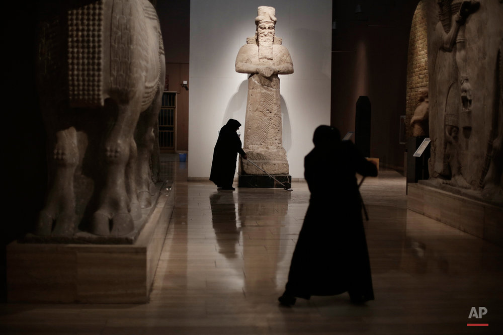 In this Sunday, March 13, 2016 photo, Iraqi workers mop the floor at the Assyrian Hall of the Iraq National Museum Baghdad. Assyria was a civilization located near the modern-day city of Mosul, now held by the Islamic State group, who published videos online showing the destruction of key Assyrian sites Nimrud and Hatra along with many other religious and cultural sites.(AP Photo/Maya Alleruzzo)