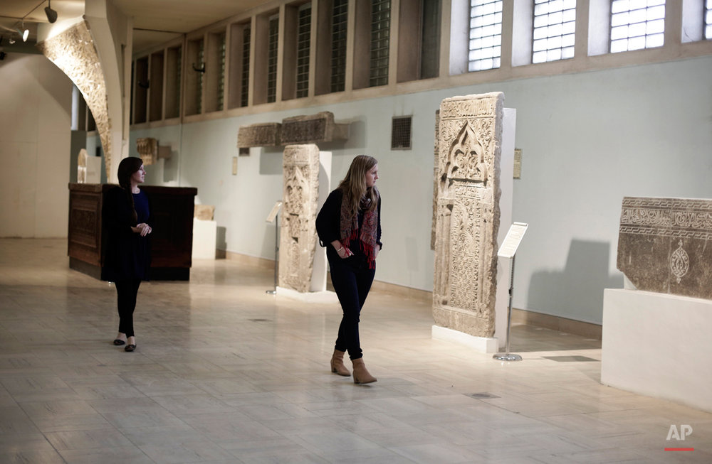 In this Sunday, March 13, 2016 photo, two women visit the Islamic Hall of the Iraq National Museum the Iraqi capital. Iraq was home to some of the most important cities of early Islam including Kufa and Karbala, and Baghdad was the capital of the Abbasid Caliphate during its golden age in the 8th and 9th centuries. The Islamic hall displays pieces of Islamic art and architecture, including a burial casket of Imam Moussa Kadhim, a major figure in Shiite Islam. Elaborate stonework from the Grand Mosque in the northern city of Mosul, now under the Islamic State group's control, is also housed here. (AP Photo/Maya Alleruzzo)