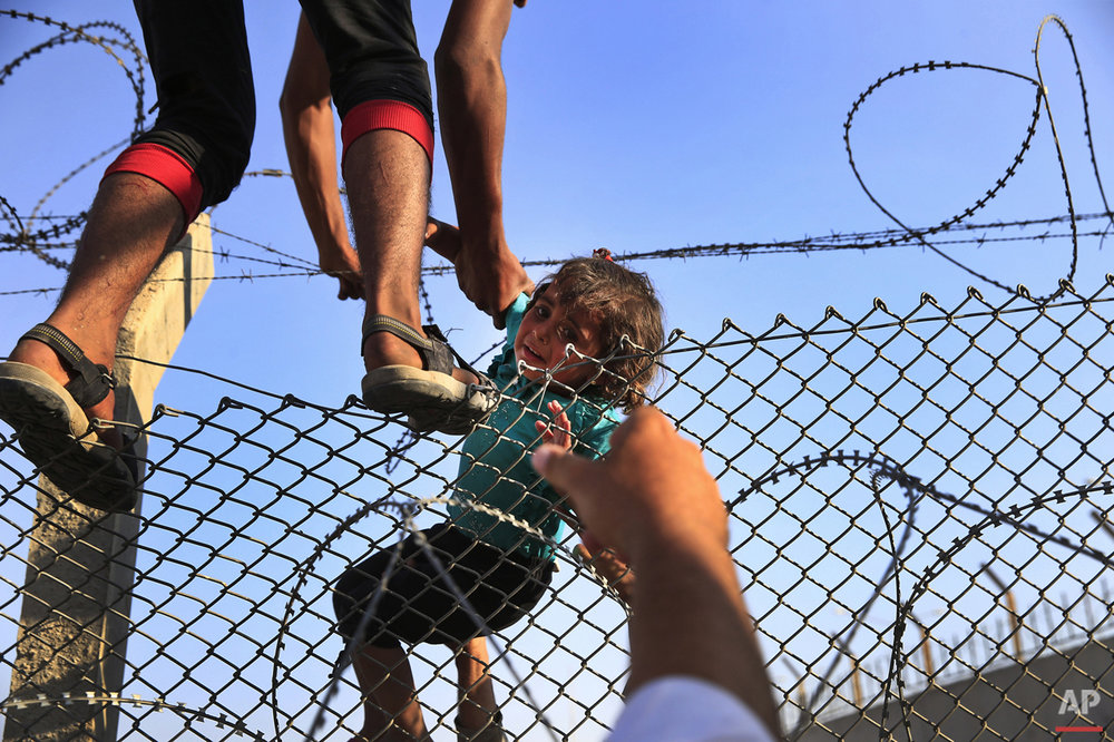 A Syrian refugee carries a baby over the border fence into Turkey from Syria in Akcakale, Sanliurfa province, southeastern Turkey,  Sunday, June 14, 2015. Thousands of Syrians cut through a border fence and crossed over into Turkey on Sunday, fleeing intense fighting in northern Syria between Kurdish fighters and jihadis.The flow of refugees came as Syrian Kurdish fighters closed in on the outskirts of a strategic Islamic State-held town on the Turkish border. (AP Photo/Lefteris Pitarakis)