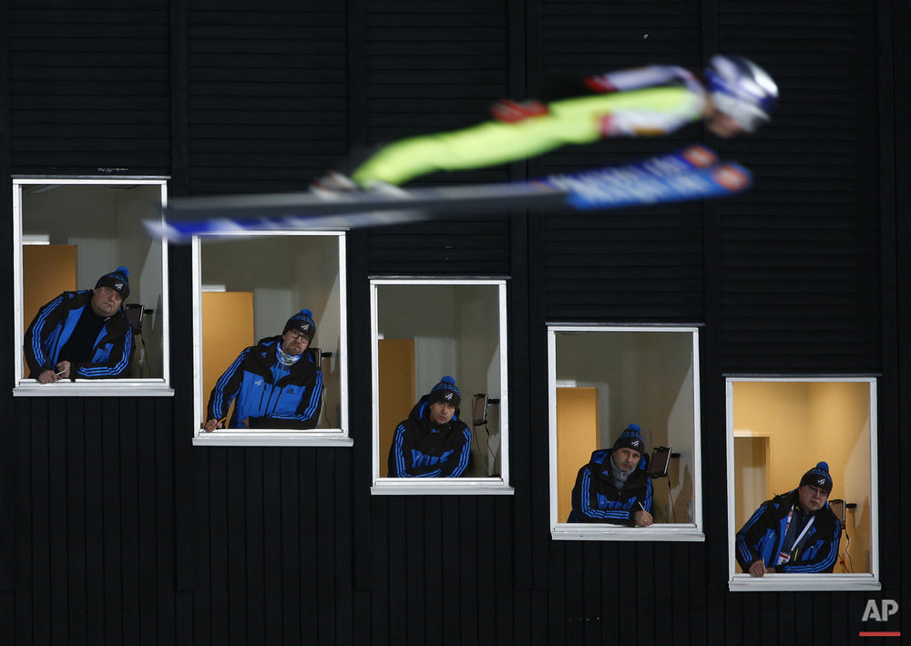 In this Sunday, Feb. 22, 2015 photo, United States' Sarah Hendrickson jumps past judges looking out of their tower windows during the Mixed Team Ski Jumping competition at the Nordic Skiing World Championships in Falun, Sweden.