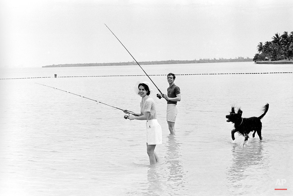 David Eisenhower, grandson of former U.S. President Dwight D. Eisenhower, and his wife Julie Nixon Eisenhower, daughter of the current President Richard M. Nixon, enjoy time off while fishing at Biscayne Bay, Fla., on May 25, 1971. With them is the president's pet irish setter King Timahoe. (AP Photo)