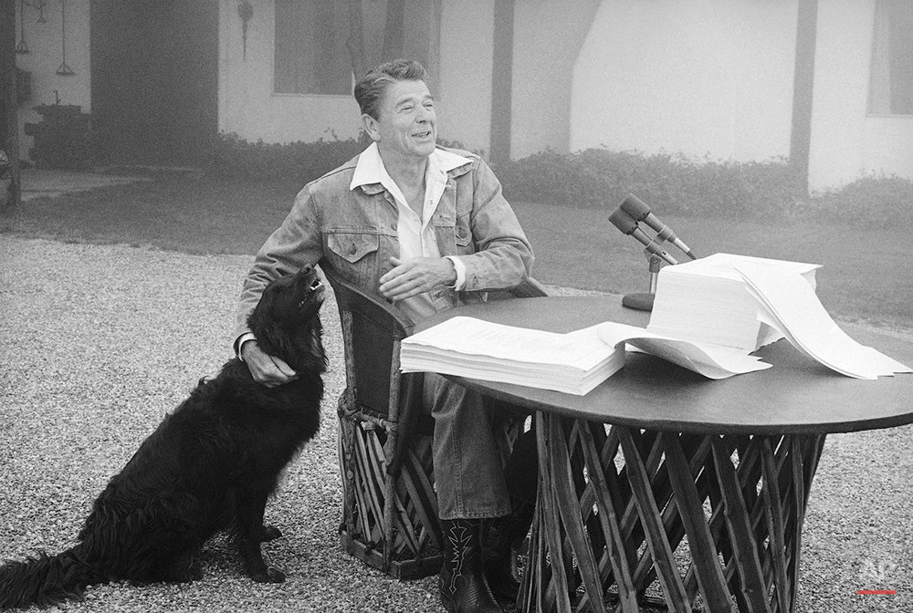 President Ronald Reagan muses with reporters and photographers after being taken by surprise by his faithful canine companion, Millie, Aug. 14, 1981 in Santa Barbara.  Millie joined her master shortly after the president completed signing landmark legislation cutting the federal budget and taxes at his California ranch near Santa Barbara. (AP Photo/Wally Fong)