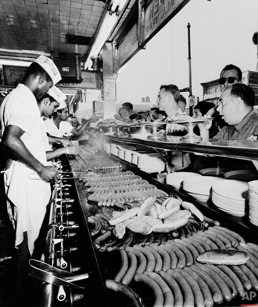 Nathan's Famous hot dogs are cooked on the grill as customers line up at Coney Island in Brooklyn, New York, on Sept. 10, 1958.  (AP Photo)