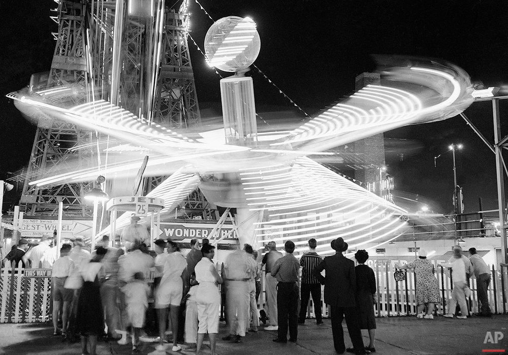 Some of the rides at Coney Island amusement park in New York on August 14, 1959, lose their identity in a whirl of lights as they carry fun-seekers around and around. (AP Photo/Ruben Goldberg)
