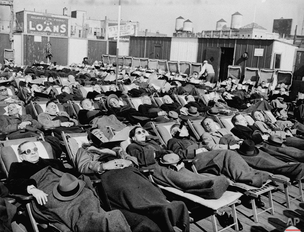 Winter sunbathing draws a crowd to the boardwalk in Coney Island, New York, on Feb. 27, 1952. (AP Photo)