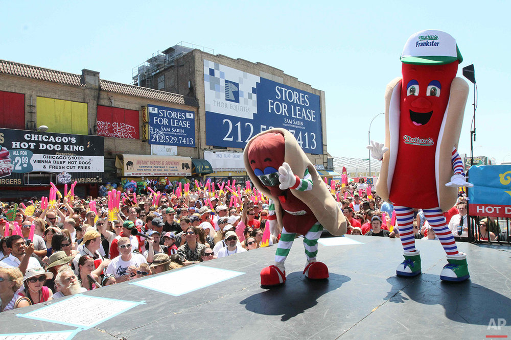 Costumed performers entertain the crowd before the start of Nathan's Hot Dog Eating Contest Sunday July 4, 2010 in the Coney Island section in the Brooklyn borough of New York. (AP Photo/Tina Fineberg)