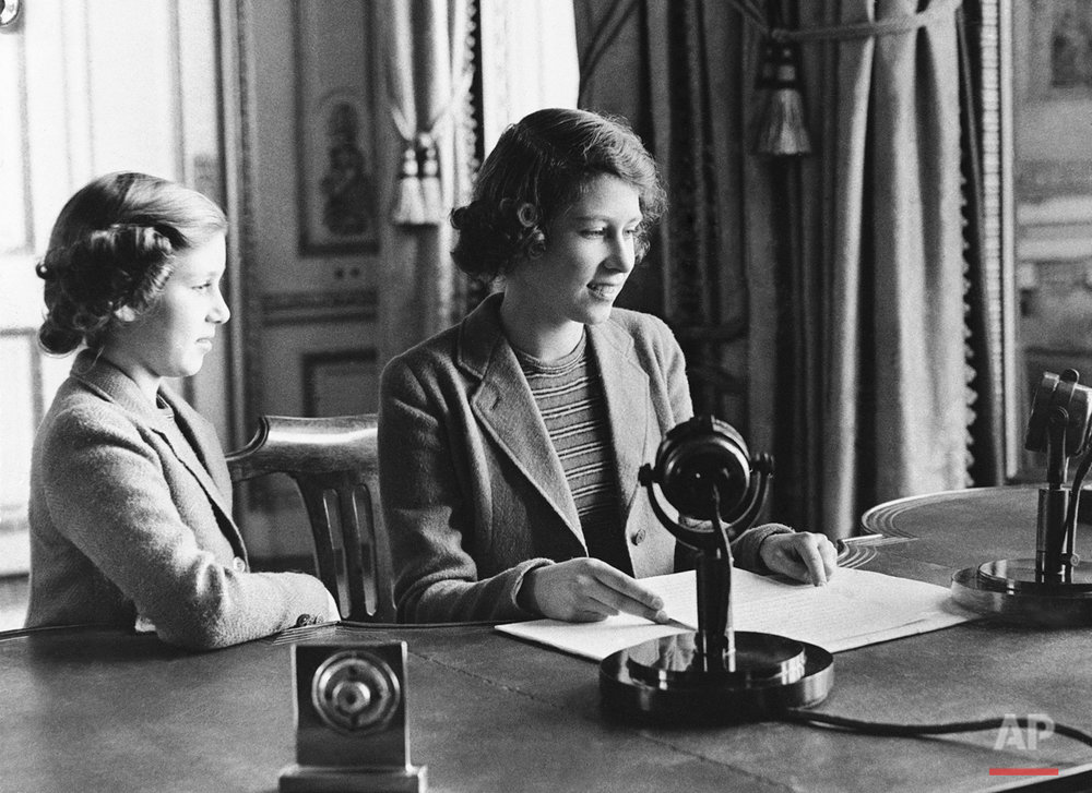 Performing one of the many public duties she will be called on, as a member of the Royal House, to fulfill as she grows older, Princess Elizabeth, center, 11-year-old heiress apparent to the British throne, is shown as she made her rapid debut, broadcasting a three-minute speech to British girls and boys evacuated overseas, Oct. 22, 1940, London, England. She is joined in bidding good-night to her listeners by her sister, Princess Margaret Rose.