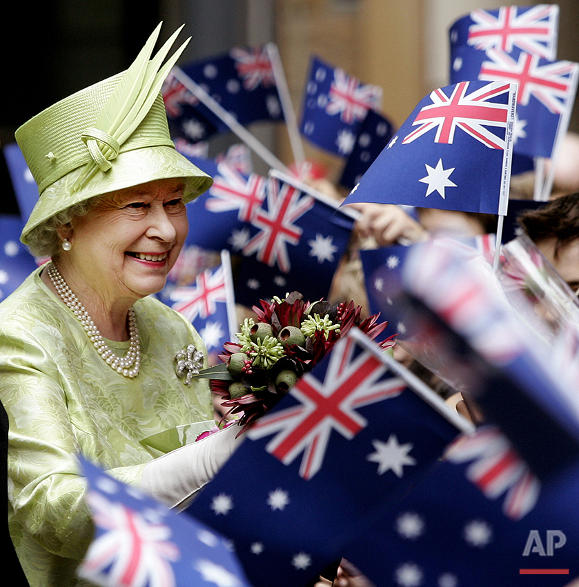 Britain's Queen Elizabeth ll,  left, receives flowers from waiting school childrenwith waiving national flags after the Commonwealth Day Service in Sydney,  Australia, Monday, March 13, 2006. The Queen will open the melbourne Commonwealth Games on March 15, 2006. (AP Photo/Rob Griffith, Pool)