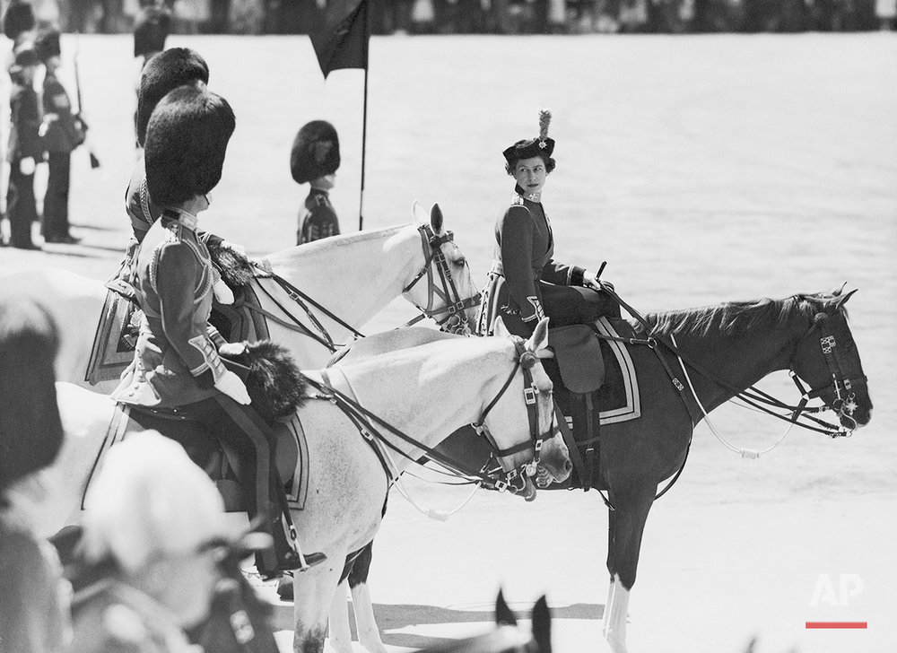 Queen Elizabeth II of Great Britain, riding side-saddle on Imp, turns to Prince Philip (nearest camera) during the ceremony of trooping the color on Horse Guards Parade in London, United Kingdom on June 13, 1957. The Duke of Gloucester, on the Queen's left, is partly hidden. (AP Photo/Eddie Worth)