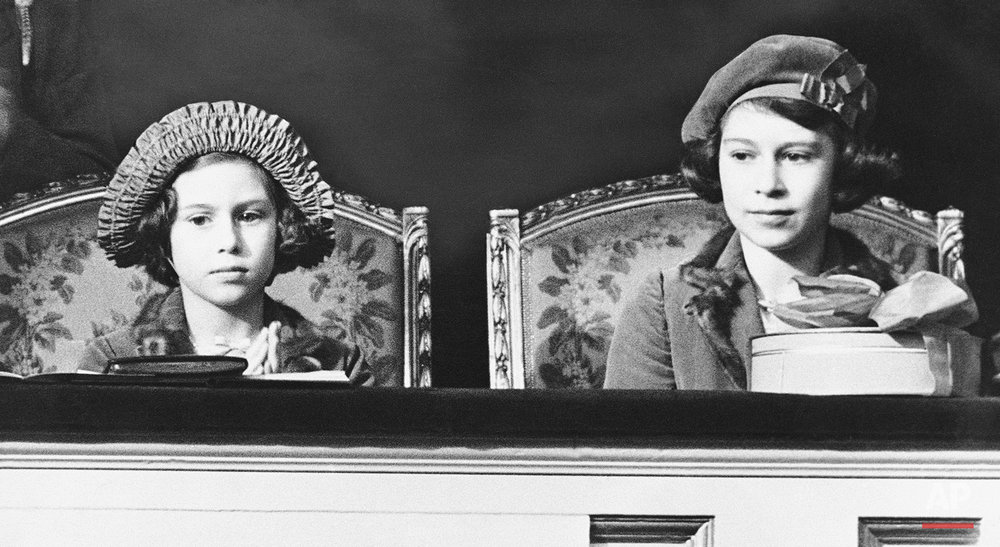 Princess Elizabeth, left, and her younger sister, Princess Margaret Rose, sit in the royal box watching the jumping at the Pony Show, March, 1938, London, England. (AP Photo)