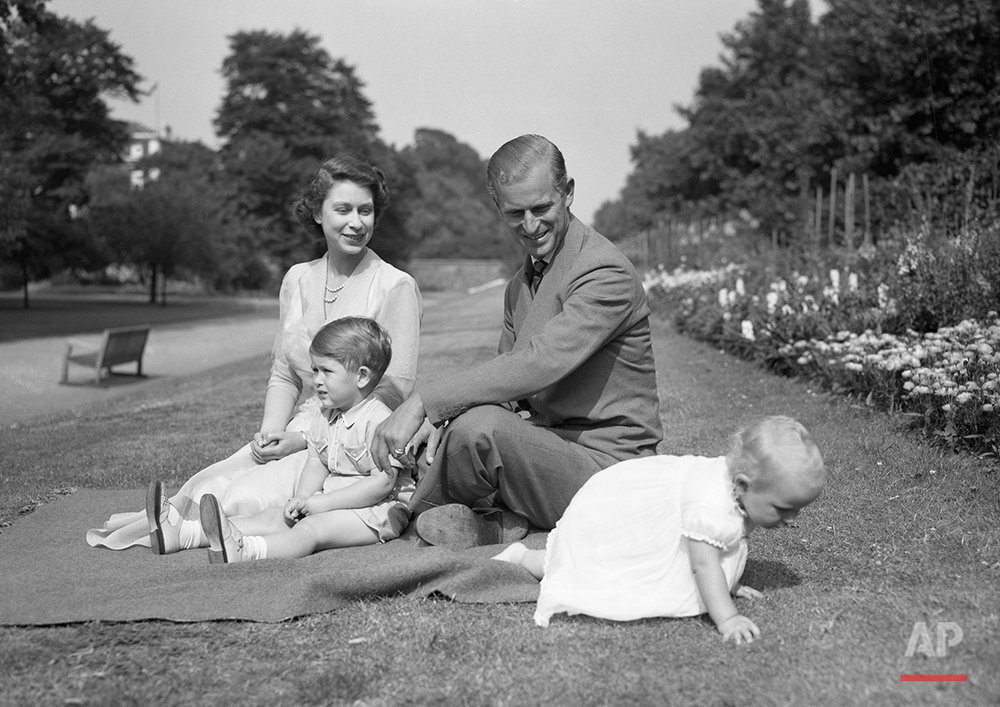 Princess Elizabeth sits with her husband Prince Philip, the Duke of Edinburgh, and Prince Charles as they watch Princess Anne try to crawl away at their London residence, Clarence House, August 8, 1951. (AP Photo/Worth)