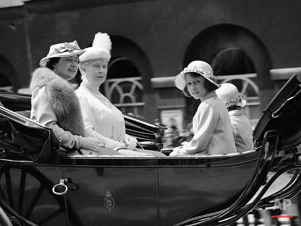 In this June 9, 1937 photo, then Britain's Queen Elizabeth, left, with Queen Mary, second left, and Princesses Elizabeth, nearest camera, and Princess Margaret, obscured right, driving from Buckingham Palace to the Horse Guards Parade for the Trooping of the Colour ceremony, in London. Britain's Queen Elizabeth celebrates her 90th birthday on Thursday, April 21, 2016. (AP Photo/Len Putnam)