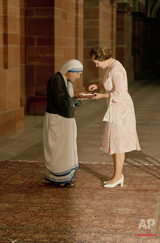 In this Thursday, Nov. 24, 1983 photo, the Queen and Mother Teresa look at the Insignia of the Honorary Order of Merit which Her majesty has just presented to the Lady of Calcutta, at the Rashtrapati Shavar, in New Delhi. Britain's Queen Elizabeth celebrates her 90th birthday on Thursday, April 21, 2016. (AP Photo)