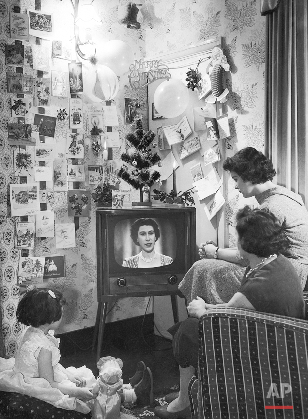 Mrs. Sidney Smart and her daughters, Sandra, 4, and Barbara, 15, look-in as Queen Elizabeth II  makes her Christmas broadcast on television on Christmas Day, Dec. 25, 1957. Her Majesty spoke from the long library at Sandringham, and was seen by both B.B.C. and I.T.V. viewers. It was the first time that the occasion has been televised. The Smart family live at Walthamstow, London, United Kingdom. (AP Photo/Sidney Smart)
