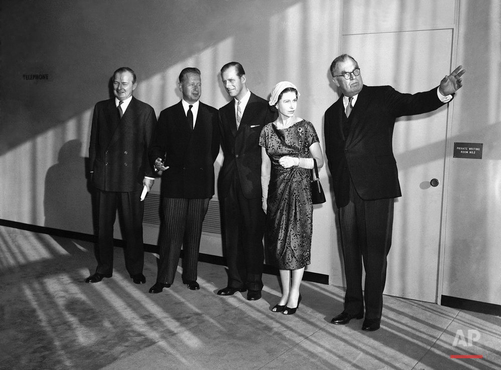 General Assembly President Sir Leslie Munro points to large windows and view from the Security Council chamber as Britain's royal couple tours United Nations headquarters in New York City on Oct. 21, 1957.   Left to Right, are: Britain's Selwyn Lloyd, U.N. Secretary General Dag Hammarskjold, Prince Philip, Queen Elizabeth II and Sir Leslie.   Sun coming through windows casts shadows on the group. (AP Photo)