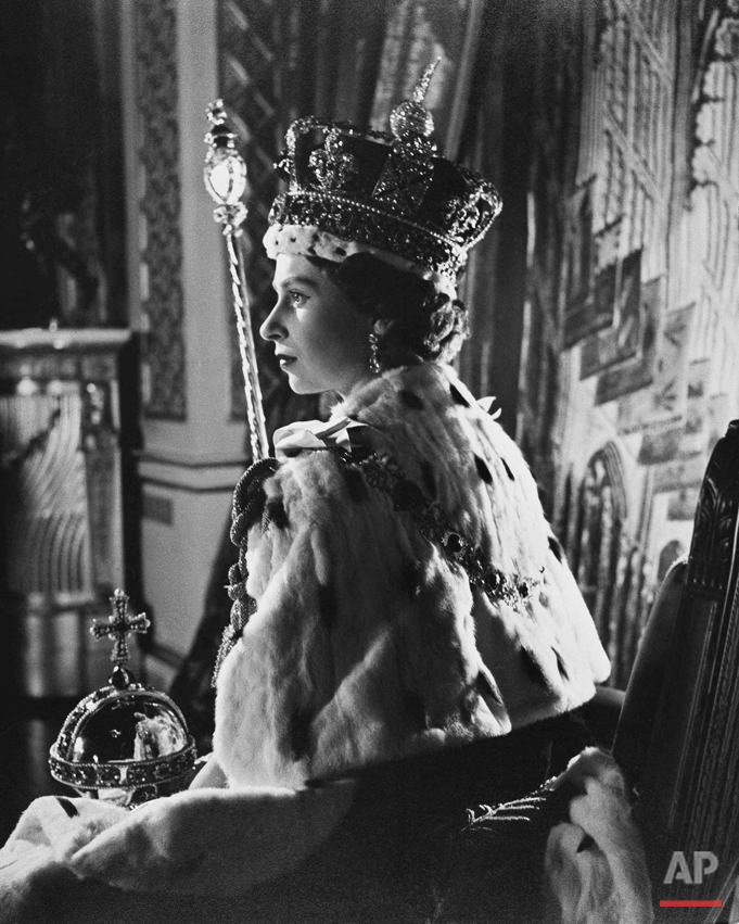 Queen Elizabeth II poses in her coronation attire in the throne room of Buckingham Palace in London, after her coronation, June 2, 1953. (AP Photo)