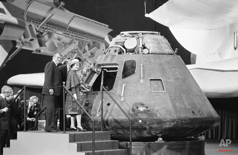 Britain's Queen Elizabeth II looks inside the Apollo 14 command module, a spaceship that visited the Moon in February 1971, during her tour of Rockwell International plant on Monday, Feb. 28, 1983 in Downey, Calif.   Guiding the Queen's tour is Rockwell board chairman Robert Anderson, left, and Rockwell North American Space Operations President George Jeffs, background. (AP Photo)