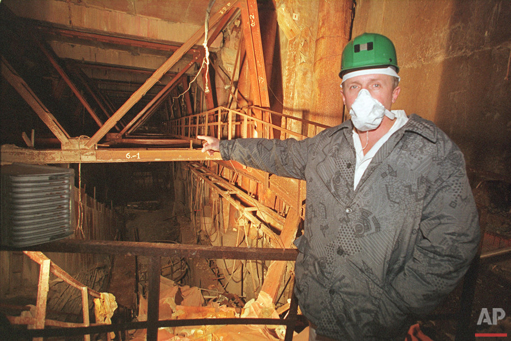In this Nov. 10, 2000 photo, an investigator points at the place of the April 26, 1986 explosion in reactor No 4 in the Chernobyl nuclear power plant, Ukraine. We reached the old control room, long and poorly lighted, with its damaged machinery, the place where the Soviet engineers threw a power switch for a routine test on that doomed night, and two explosions followed. (AP Photo/Efrem Lukatsky)