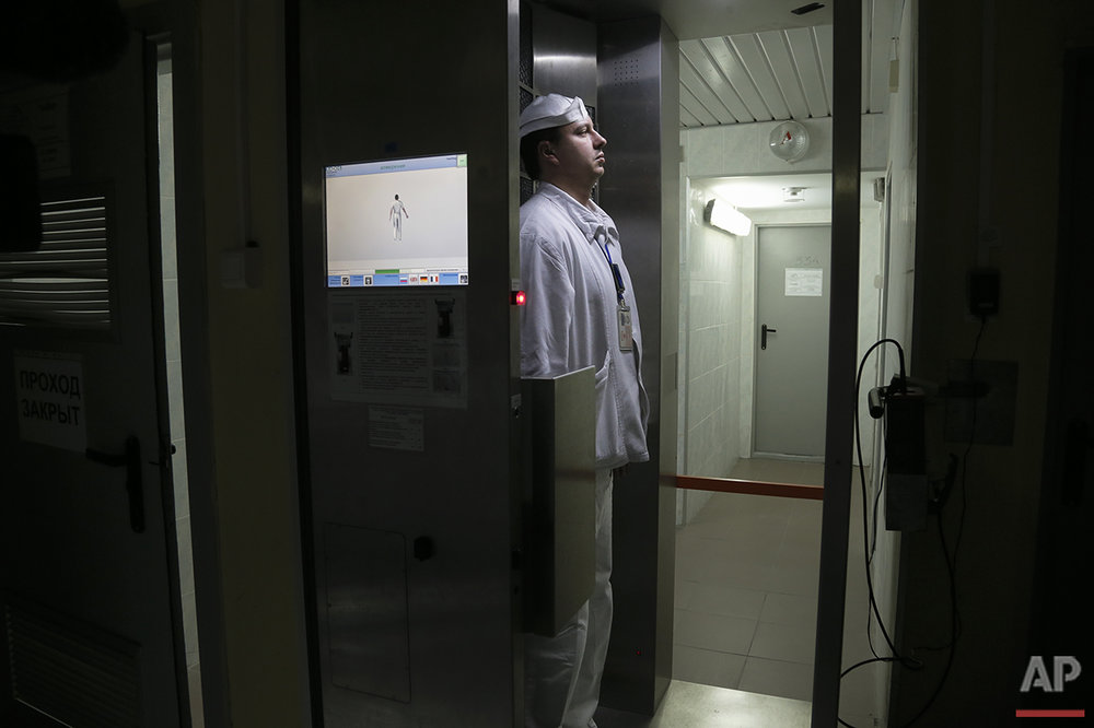 In this photo taken on Wednesday, March  23, 2016, a worker checks radiation levels after he leaves the nuclear waste storage at the Chernobyl nuclear power plant in Chernobyl, Ukraine. The half-life of cesium-137, one of the most dangerous of the particles emitted by the explosion, is 30 years -- as long as it has been since the blast. At least three more of those half-lives will have to pass before the soil might be considered uncontaminated. (AP Photo/Efrem Lukatsky)