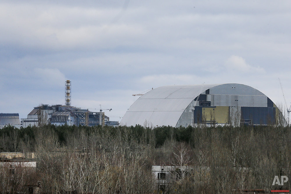 In this photo taken on Wednesday, March  23, 2016, a chimney over the destroyed reactor at the Chernobyl nuclear power plant, background left, and a gigantic steel-arch under construction to cover the remnants of the exploded reactor, are seen in the town of Prypyat close to Chernobyl, Ukraine. Abandoned houses in the foreground were left by Chernobyl plant workers a few days after the explosion, and since then Prypyat has become the ghost town. Ukraine marks the 30th anniversary of the world's worst nuclear disaster on April 26. (AP Photo/Efrem Lukatsky)