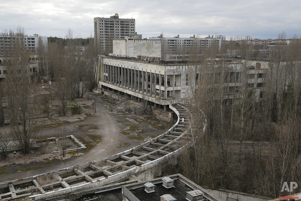 This photo taken Wednesday, March 23, 2016 shows abandoned apartment buildings in the town of Pripyat near Chernobyl, Ukraine, with a chimney, left, at the destroyed reactor and a gigantic  arch-shape confinement to cover the remnants of the exploded reactor, in the back, at the Chernobyl nuclear power plant. Thirty years after the world's worst nuclear accident, the Chernobyl nuclear power plant is surrounded by both a hushed desolation and clangorous activity, the sense of a ruined past and a difficult future. (AP Photo/Efrem Lukatsky)