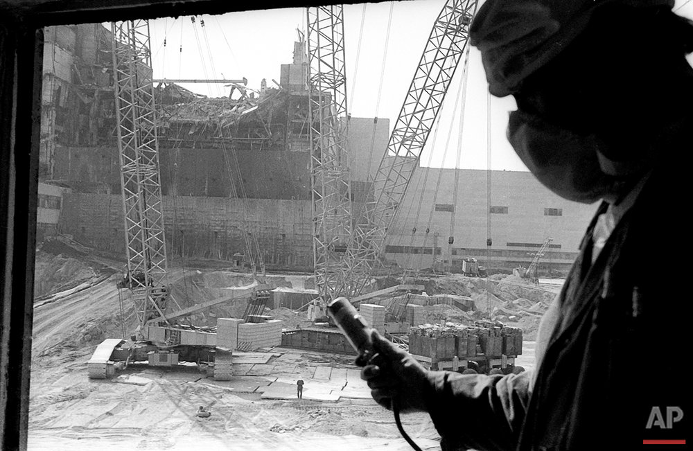 In this 1986 photo, a Chernobyl nuclear power plant worker holding a dosimeter to measure radiation level is seen against the background of a sarcophagus under construction over the 4th destroyed reactor, Ukraine. On May 12, 1986, more than two weeks after the explosion, the leading Soviet daily newspaper Pravda published its first photograph from the site for the first time, shot three days earlier from a helicopter.  (AP Photo/Volodymyr Repik)