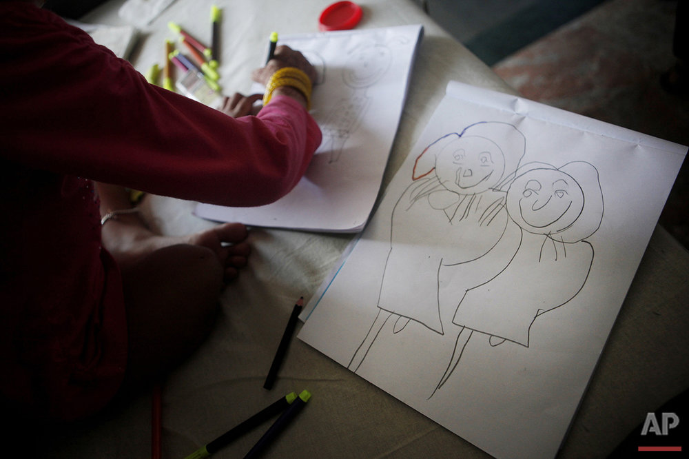 In this July 24, 2015 photo, Nepalese girl Nirmala Pariyar, 8, draws pictures of herself and her friend Khendo Tamang, also 8, at the Bir Trauma Center in Kathmandu, Nepal. (AP Photo/Niranjan Shrestha)