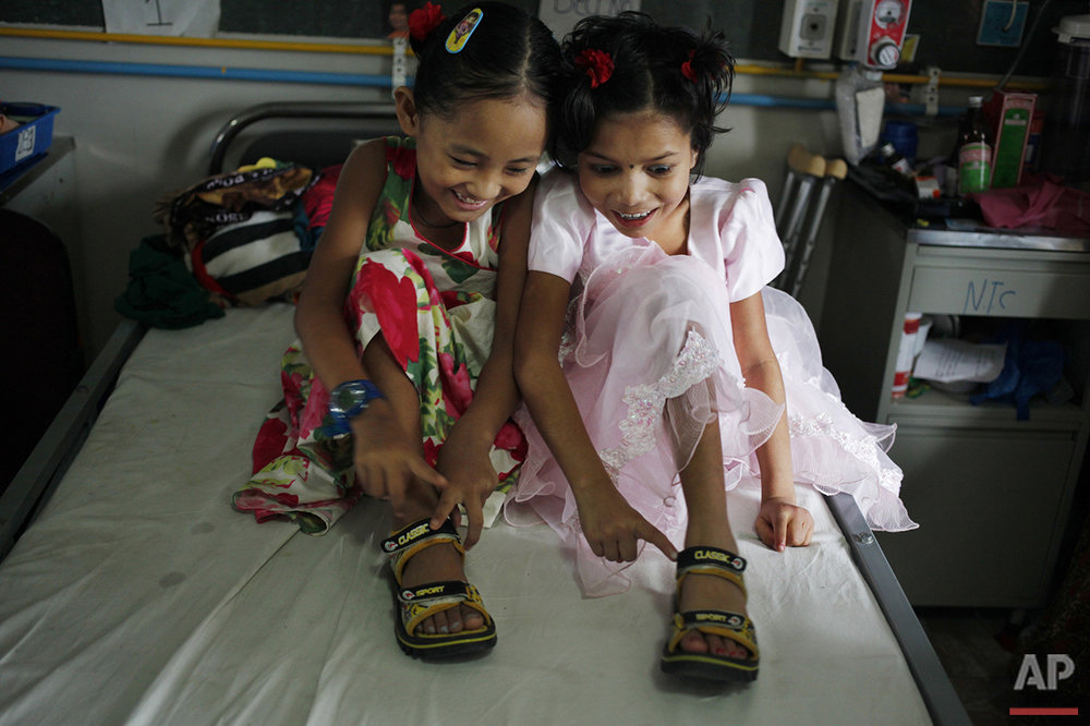 In this July 15, 2015 photo, Nepalese amputee victims Khendo Tamang, left, and Nirmala Pariyar, both 8, share a single pair of shoes at the Bir Trauma Center in Kathmandu, Nepal. After suffering serious leg wounds in Nepal's massive 2015 earthquake that killed and injured thousands, both girls were brought to the Bir Trauma Center in Kathmandu, to receive single leg amputations. Following their surgeries, Nirmala's relentless cheerfulness drew a still very depressed Khendo close and both found an inseparable friendship which has helped their emotional wounds heal. (AP Photo/Niranjan Shrestha)