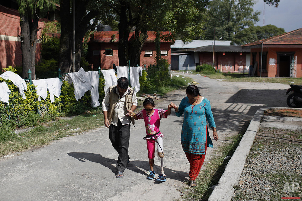 In this Oct. 16, 2015 photo, amputee victim in the massive 2015 Nepal earthquake, Khendo Tamang, 8, center, walks with the assistance of her mother Yagnsen and family friend Chitra Bahadur after receiving a new prosthesis at a clinic in Kathmandu, Nepal. (AP Photo/Niranjan Shrestha)