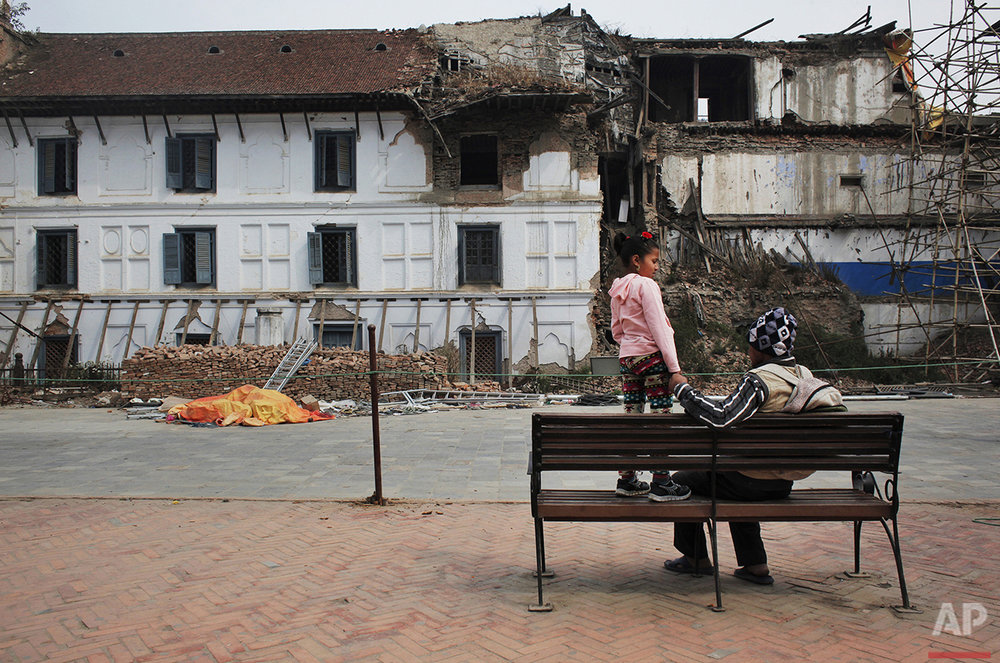In this March 12, 2016 photo, Chitra Pariyar and his daughter Nirmala, 8, rest on a bench in Basantapur Durbar Square, Kathmandu, Nepal. Nirmala lost a leg in Nepal's massive April 2015 earthquake that killed nearly 9,000 people dead and more than 22,000 injured. (AP Photo/Niranjan Shrestha)