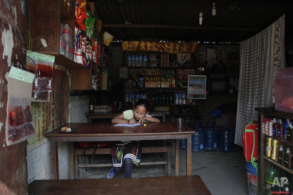 In this April 20, 2016 photo, Nepalese earthquake amputee victim Khendo Tamang, 8, studies at her aunt's shop in Kathmandu, Nepal. (AP Photo/Niranjan Shrestha)